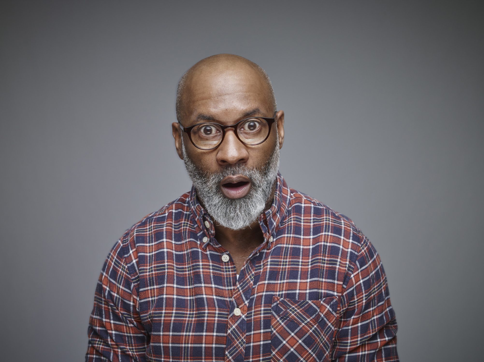 Portrait of astonished man wearing spectacles and checked shirt in front of grey background