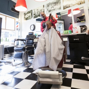 Black barber clipping hair of boy in retro barbershop