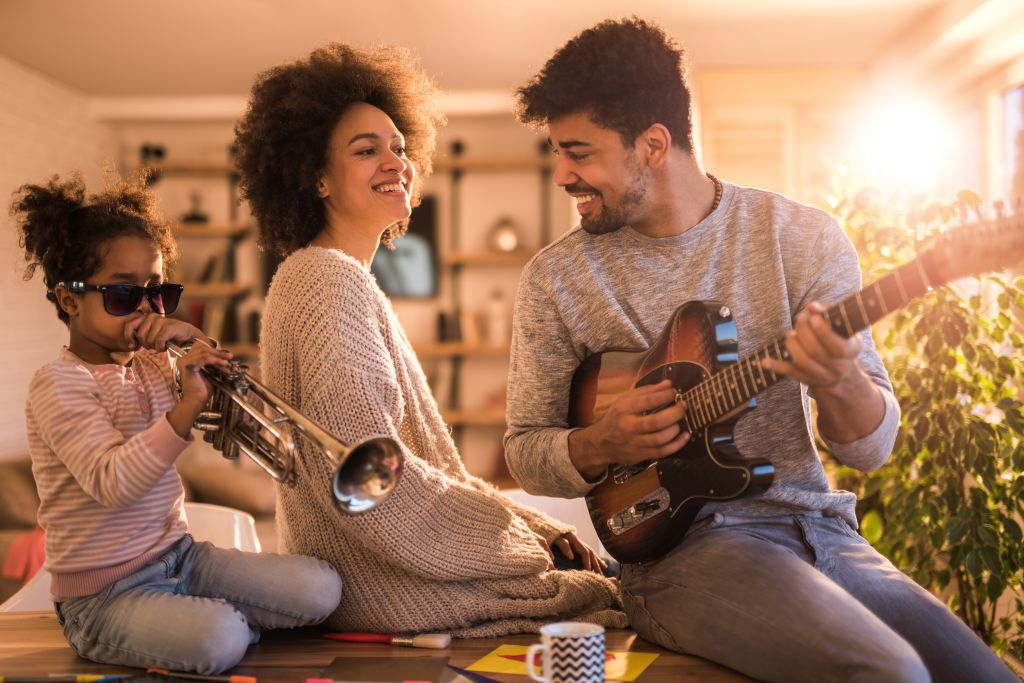 Playful black family having fun while playing musical instruments at home.