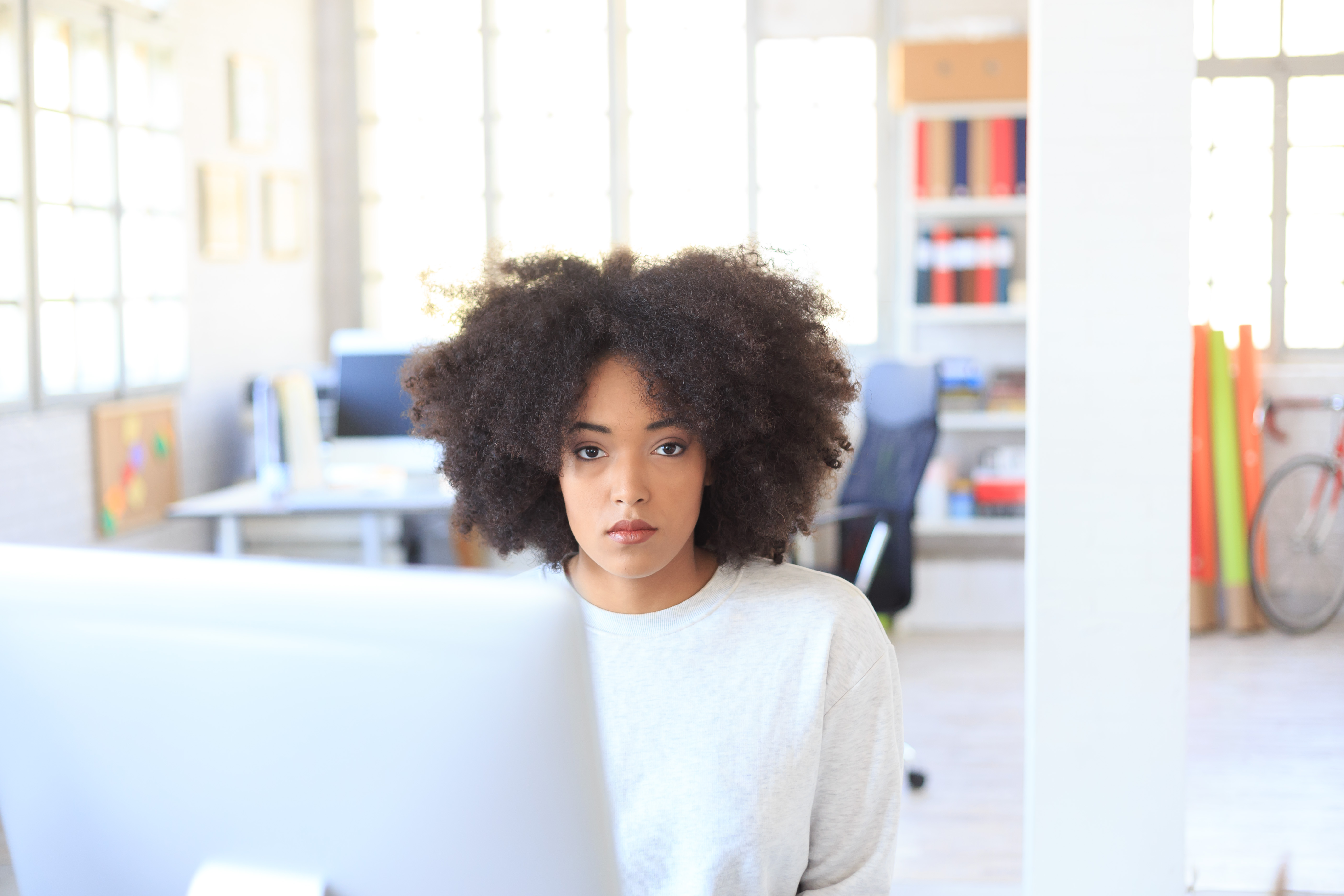 Young african woman sitting at workplace