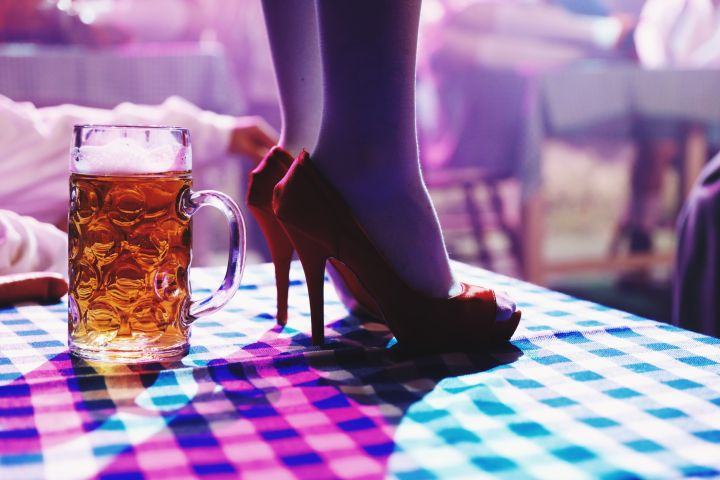 Low Section Of Woman Standing By Beer Glass On Table At Bar
