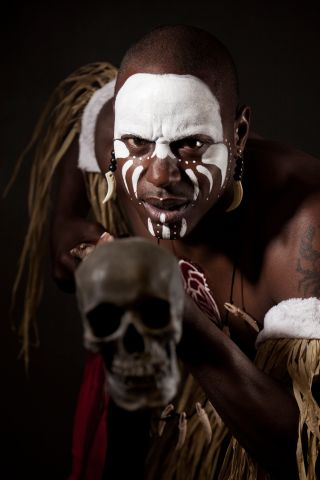 African witch doctor with bodypaint in dramatic light