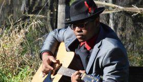 Man Wearing Suit Playing Guitar While Sitting In Yard