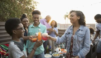 African American family toasting soda glasses, enjoying barbecue on summer deck