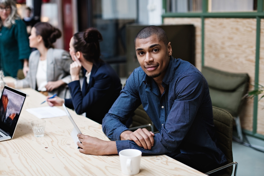 Portrait of young businessman sitting with female colleagues at table in office meeting