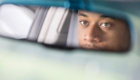 Partial reflection of man looking in rear view mirror
