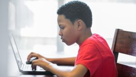 Young teenage boy working on homeschool assignments using laptop at home