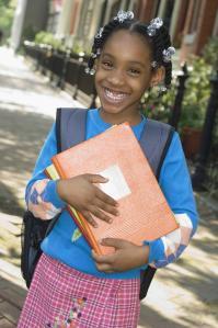 African girl holding school books